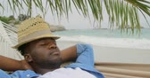 голова и плечи : High angle view of African american man sleeping in a hammock on the beach. He is asleep 4k Стоковые видеозаписи
