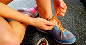 health awareness : Closed-up of Caucasian woman tying shoelaces in a fitness studio. She is getting ready for exercise. 4k Stock Footage