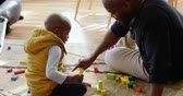 domicílio : Side view of African american father and son playing with building blocks in a comfortable home. They are sitting on the floor. 4k
