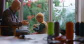 três quarto comprimento : Side view of Caucasian father and son stitching keychain at home. Various thread rolls on a table in the foreground. 4k