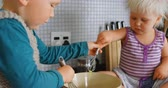 žloutek : Close-up of Caucasian siblings stirring eggs with whisker in kitchen at home. They are preparing food 4k