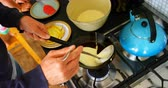 cocina de gas : Close-up of Caucasian man preparing pancake in kitchen at home. Man pouring pancake dough on pan 4k
