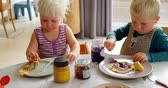real jam : Front view of Caucasian siblings eating pancakes while sitting at dining table at home. 4k