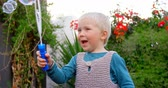 длина : Front view of Caucasian boy playing with bubble wand in garden. He is smiling and having fun 4k