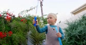 elülső : Front view of Caucasian boy playing with bubble wand in garden. He is smiling and having fun 4k
