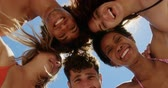 amontoado : Low angle view of young multi ethnic friends forming huddle while Low angle view of young multi ethnics friends forming huddle while smiling and looking at camera at beach in the sunshine at beach in the sunshine 4k