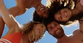 amontoado : Low angle view of young multi ethnic friends forming huddle while smiling and looking at camera at beach in the sunshine 4k