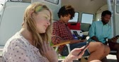 furgone : Side view of young multi ethnic friends using mobile phone near camper van at beach on a sunny day 4k Filmati Stock