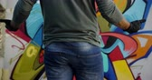 grafiti : Mid section of Caucasian graffiti artist standing in front of graffiti wall. He is gesturing hands 4k