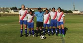amateurvoetbal : Front view of diverse female soccer team standing arm to arm on soccer field on sunny day. 4k