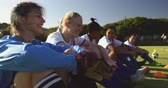 amateur : Side view of happy diverse female soccer players sitting on the ground while talking on soccer field. 4k