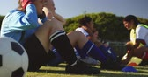 amateur : Side view of diverse female soccer team doing sit up exercises while mixed race captain gives training on soccer field. 4k Stock Footage