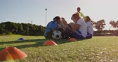 amateurvoetbal : Side view of diverse female soccer team doing sit up exercises while mixed race captain gives training on soccer field. 4k Stockvideo