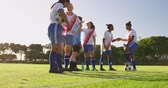 tonificado : Side view of diverse female soccer team in break time talking to each other while drinking and holding ball on soccer field 4k