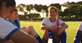 concentrar : Front view of diverse female soccer team in break talking to teammates and laughing. 4k