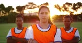 amateurvoetbal : Front view of concentrated diverse female soccer team in orange vests standing with arms crossed on soccer field. 4k