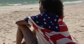 three generation : Side view of African american couple wrapped in American flag sitting together on the beach. They are looking at sea 4k