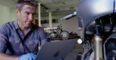 резервный : Front view of Caucasian male mechanic using laptop in motorbike repair garage. He is looking at motorbike 4k