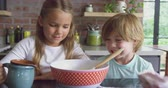 biscoitos : Close-up of Caucasian siblings preparing cookie on worktop in kitchen at comfortable home. Girl pouring water in bowl 4k