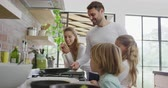 utensil : Side view of Caucasian family preparing food in kitchen at home. Father holding pan 4k Stock Footage