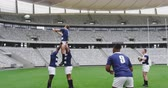 concorrente : Side view of diverse male rugby players playing rugby match in stadium. They are passing rugby ball 4k