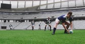 závodník : Front view of diverse male rugby players playing rugby match in stadium. Caucasian male player passing rugby ball 4k