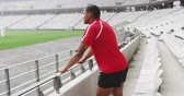конкурент : Side view of African american male rugby player standing in stadium. He is looking away 4k