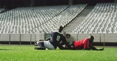 concorrente : Side view of African American rugby players playing rugby match in stadium. They are tackling each other 4k