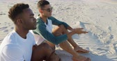 suntan : Elevated close up view of an African American and an Asian young man sitting on a beach talking and looking out to sea. Young friends having summer fun on the beach together 4k