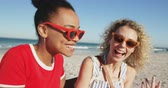 suntan : Close up side view of two female friends, a young African American and a young Caucasian woman, sitting on a beach wearing sunglasses, talking and embracing. Young friends having summer fun on the beach together 4k Stock Footage