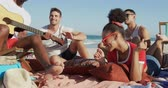 suntan : Close up of a multi-ethnic group of happy young adult male and female friends, sitting on a beach together listening to a young African AMerican man singing and playing playing a guitar. Young friends having summer fun on the beach together 4k