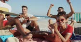 suntan : Close up of a multi-ethnic group of happy young adult male and female friends, sitting on a beach together listening to a young African American man singing and playing a guitar. Young friends having summer fun on the beach together 4k