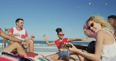 beach ball : Close up of a multi-ethnic group of happy young adult male and female friends hanging out on a beach together, playing with a ball and playing guitar. Young friends having summer fun on the beach together 4k