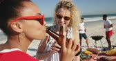 amusing : Close up of two female friends, a young African American and a young Caucasian woman, standing on a beach wearing sunglasses, laughing and drinking beers. Young friends having summer fun on the beach together 4k