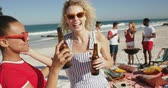 suntan : Close up front view of two female friends, a young African American and a young Caucasian woman, standing on a beach wearing sunglasses, making a toast with their beer botttes and embracing. Young friends having summer fun on the beach together 4k