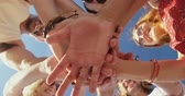 suntan : Low angle close up portrait of a group of multi-ethnic male and female young adult friends standing in a circle looking down at the camera smiling with their hands together in the centre, and raising them together. Young friends having summer fun on the b