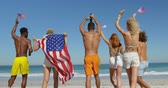 suntan : Close up back view of a multi-ethnic group of happy young adult friends dancing on a beach, waving US flags and raising their arms in the air. Young friends having summer fun on the beach together 4k