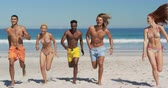 bronzlaşmış : Front view of a multi-ethnic group of young adult friends running on a beach. Young friends having summer fun on the beach together 4k Stok Video