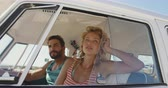 off road : Close up of a young Caucasian couple sitting in the front seat of a camper van at a beach relaxing and looking out of the window. Summer Road Trip in Camper Van to the beach with friends 4k