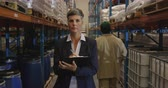 distribution : Portrait of a middle aged Caucasian female warehouse manager checking stock, standing by shelves in a warehouse, and smiling to camera. A warehouse worker walks past her. They are working in a freight transportation and distribution warehouse. Industrial