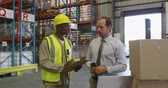 panoya : Front view of a middle aged Caucasian male warehouse manager holding a barcode scanner and a young African American male warehouse worker holding a clipboard standing by a stack of boxes in a warehouse loading bay talking, looking at a laptop computer, po