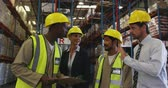 panoya : Front view close up of middle aged Caucasian female and male warehouse managers, a young African American and a young Asian male manual worker having a meeting in the loading bay of a warehouse, talking and looking at a clipboard, and then walking away. T