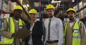 colegas de trabalho : Portrait of middle aged Caucasian female and male warehouse managers, a young African American and a young Asian male manual worker. They are all wearing yellow hard hats, looking at a clipboard and look up to camera smiling, standing in the loading bay o