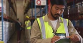 буфер обмена : Front view close up of a young Asian male warehouse worker writing on a clipboard in a warehouse and walking out of shot. In the background warehouse staff are standing near the storage shelves talking. They are working in a freight transportation and dis