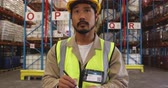 ládakeret : Close up of a young Asian male warehouse worker wearing a yellow hard hat wiriting on a clipboard standing in a warehouse loading bay. Storarge shelves are visible in the background. They are working in a freight transportation and distribution warehouse.