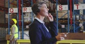 panoya : Close up side view of a middle aged Caucasian female warehouse managerusing a two-way radio headset and writing on a clipboard in a warehouse loading bay. In the background warehouse staff walk past the storage shelves. They are working in a freight trans
