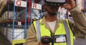 amusing : Close up of a young Asian male warehouse worker wearing a VR headset, holding barcode scanner and smiling in a warehouse loading bay. They are working in a freight transportation and distribution warehouse. Industrial and industrial workers concept 4k Stock Footage