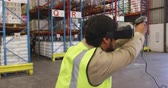 amusing : Close up front view of a young Asian male warehouse worker jumping around playing with a VR headset and barcode scanner in a warehouse loading bay. In the background a male worker walks past watching him in disbelief. They are working in a freight transpo
