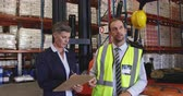 panoya : Front view close up of a middle aged Caucasian female and middle aged Caucasian male warehouse manager standing by a forklift in a warehouse loading bay pointing to shelves and talking, she is holding a clipbaord and writing. They are working in a freight