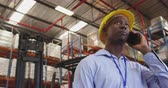 ládakeret : Close up low angle of a young African American man wearing a yellow hard hat talking on a smartphone in a warehouse. They are working in a freight transportation and distribution warehouse. Industrial and industrial workers concept 4k
